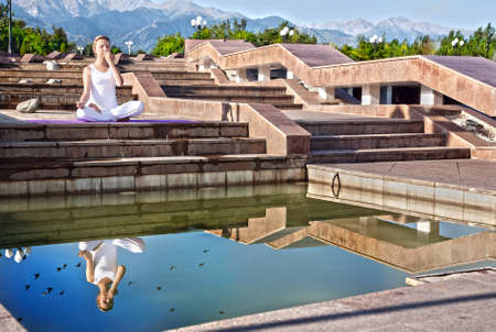 dhyana: Beautiful Caucasian woman in white cloth doing nadi suddhi pranayama with Pranav mudra in ardha padmasana, half lotus pose. Woman Sitting on the stone stairs near the water with her reflection at Mountain background Stock Photo