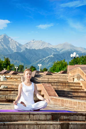 dhyana: Beautiful Caucasian woman in white cloth doing meditation in ardha padmasana, half lotus pose with dhyana mudra gesture. Woman Sitting on the stone stairs at Mountain background Stock Photo