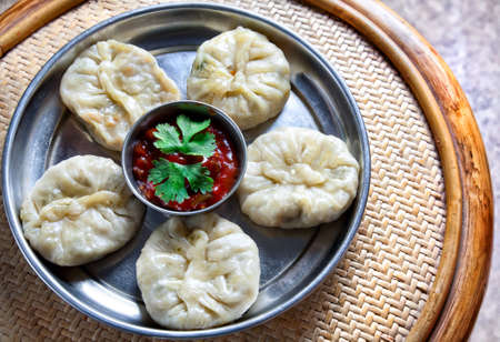 Tibetan traditional dumpling momo served with red chatni on the small wooden table Stock Photo