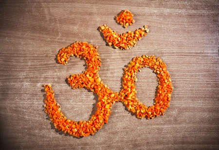 Om symbol from chopped carrot on the textured table represent pure vegetarian cuisine photo