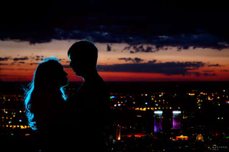 evening glow: Young couple silhouette hugging and looking at each other outdoors at night neon city background