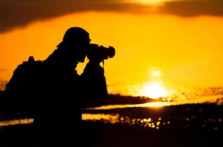 Photographer silhouette shooting sea outdoors at sunset background Stock Photo - 10440723