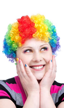 Beautiful woman in rainbow clown wig and creative rainbow make-up smiling and looking aside at white background photo