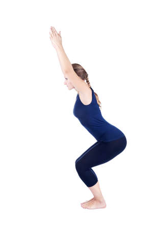 side pose: Beautiful Caucasian woman doing utkatasana, chair powerful pose at white background