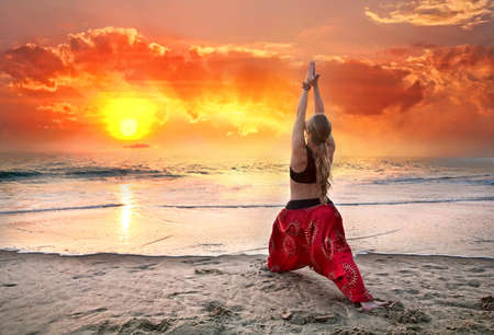 Beautiful woman doing virabhadrasana I, warrior yoga pose on the beach near the ocean at sunset in India