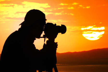 photographing: Photographer silhouette shooting sea outdoors at sunset background