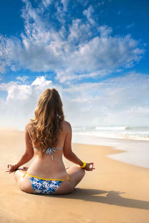 Beautiful Caucasian woman in swimwear sitting in padmasana meditation lotus pose photo