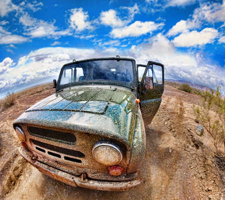 kazakhstan: Dirty vehicle in desert with opened doors and blue sky background in Altyn Emel national park in Kazakhstan