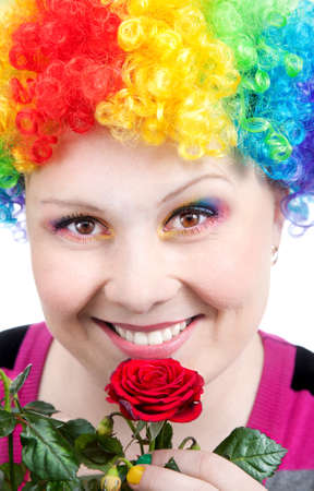 Beautiful woman in rainbow clown wig and creative rainbow make-up smiling and looking at camera with red rose at white background photo