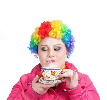 woman drinking tea: Beautiful woman in rainbow clown wig and creative rainbow make-up holding cup of tea and breathing in the steam at white background. Free space for text