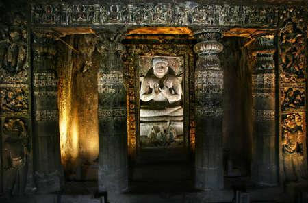 maharashtra: Buddha statue sitting inside Ajanta Cave with glowing walls in Maharashtra, India