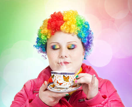 Clown in rainbow wig and creative rainbow make-up holding cup of tea and breathing in the steam at multicolored bokeh background Stock Photo - 10572898