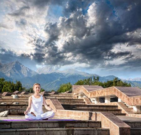 dhyana: Donna che fa meditazione yoga in panno bianco. Ardha padmasana, mezzo loto posare con gesto dhyana mudra. Donna seduta sulle scale di pietra alla montagna e drammatico sfondo nuvole