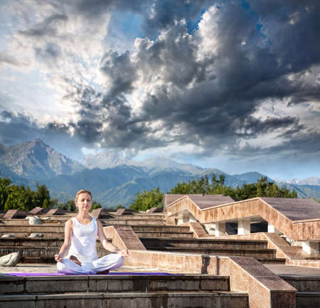 dhyana: Woman doing yoga meditation in white cloth. Ardha padmasana, half lotus pose with dhyana mudra gesture. Woman Sitting on the stone stairs at Mountain and dramatic clouds background Stock Photo