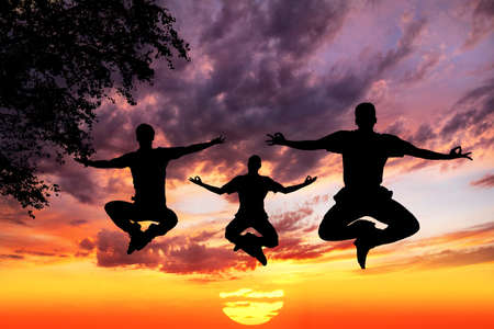 padmasana: Three Men silhouettes doing yoga padmasana lotus pose in jumping with tree nearby outdoors at sunset background
