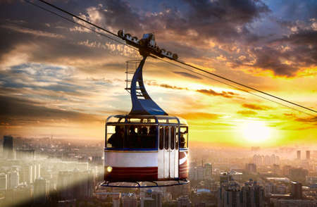 ropeway: funicular with light lifting up by ropeway and view of city at dramatic sunset sky background