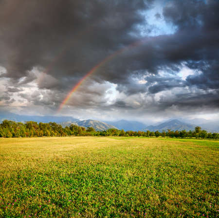 Rainbow under grass field, trees and mountains at dramatic storm sky with dark clouds background photo