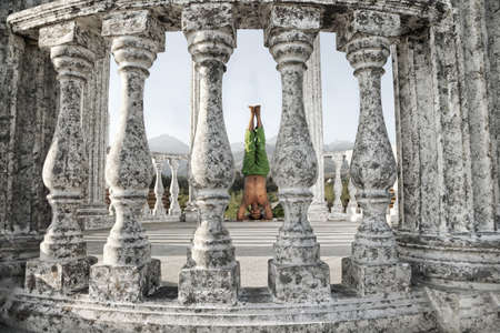 shirshasana: Yoga shirshasana, head stand pose is done by Indian man in green trousers between stone columns at mountain background