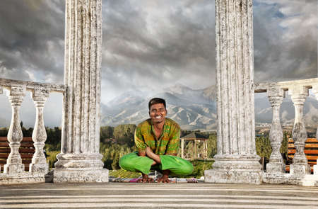 Yoga Kukkutasana, cockerel pose is done by smiling Indian man in green cloth near stone column at mountain and dramatic sky background photo