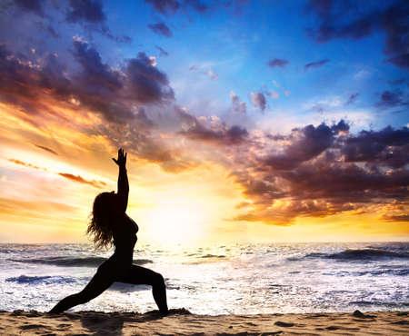 Mooie Vrouw silhouet doet Virabhadrasana ik warrior in de buurt pose op het zand strand en de oceaan bij zonsondergang achtergrond in India, Goa