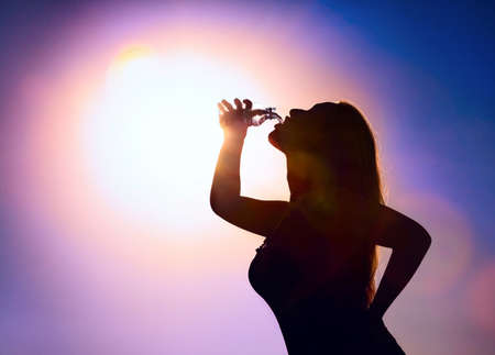 Woman silhouette drinking water from the bottle at purple sky and big sun background photo