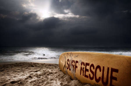 lifeguard: Surfboard with title surf rescue on the beach near the ocean at dramatic storm sky with dark clouds background Stock Photo