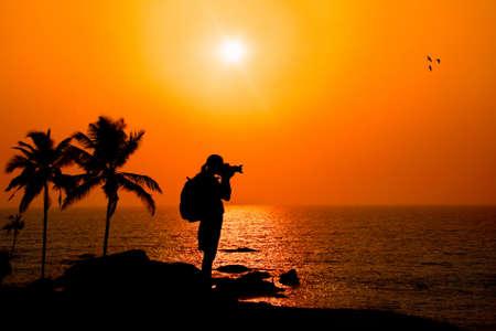 海の夕日を背景でヤシの木の近くの岩の崖に屋外での撮影写真家シルエット 写真素材