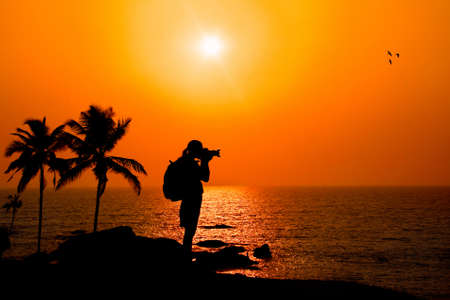 Photographer silhouette shooting sea outdoors on the rock cliff near palm trees at sunset background