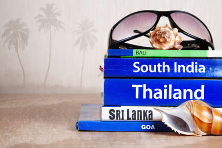 travel guide: Guide books on the table with Seashells and sunglasses on its at palm trees and ocean background. Books with titles: South India, Bali, Sri Lanka, Goa, Thailand Stock Photo