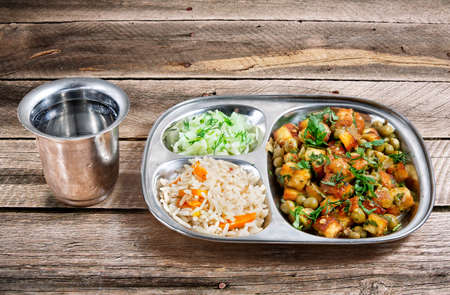paneer: Mutter paneer, fried rice, cucumber salad and glass of water: delicious traditional Indian food on wooden table Stock Photo