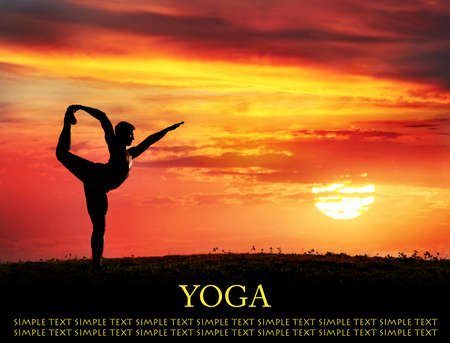 Yoga Natarajasana dancer balancing pose by Man in silhouette with dramatic sunset sky background. Free space for text