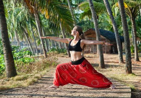kerala: Yoga virabhadrasana II warrior pose by beautiful Caucasian woman in red Indian trousers with symbol om on the road in palm tree forest with house at background in India, Kerala, Varkala
