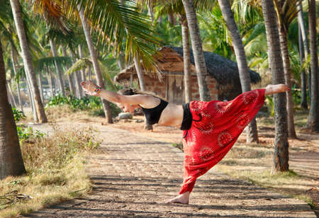 kerala: Yoga virabhadrasana III warrior pose by beautiful Caucasian woman in red Indian trousers with symbol om on the road in palm tree forest with house at background in India, Kerala, Varkala Stock Photo