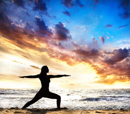 virabhadrasana II warrior pose by beautiful Woman silhouette on the sand beach and ocean nearby at sunset background in India, Goa Stock Photo