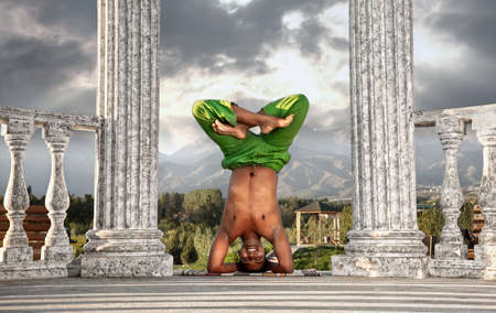 shirshasana: Yoga urdhva padmasana, head standing pose in lotus by smiling Indian man in green trousers near stone column at mountain and dramatic sky background