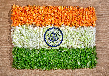 Indian national flag from chopped raw vegetables: carrot, cabbage and green beans on the textured table represent pure vegetarian cuisine photo