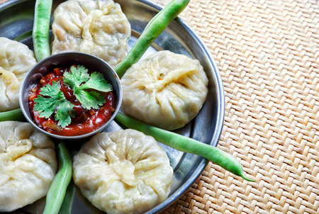 Tibetan traditional dumpling momo served with red chatni and green raw beans on the small wooden table. Free space for your text Stock Photo - 10714757