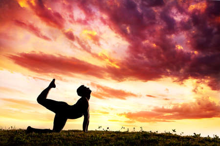parshva marjariasana cat pose by Man silhouette outdoors at sunset background. Free space for text photo