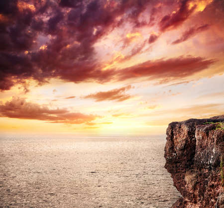 Beautiful background of ocean, cliff and sunset orange sky with clouds. Free space for text or man Stock Photo - 10714761