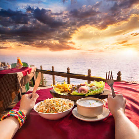 vegs: Indian vegetarian sizzler, corn soup and fried rice on the table at ocean and dramatic sunset background. Hands with fork and knife on the table Stock Photo