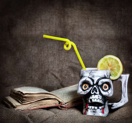 haloween: Skull mug with lemon and yellow stick near old book at textured background on Halloween party
