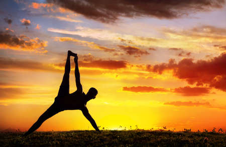 Yoga Vasisthasana plank balancing pose by Man in silhouette with dramatic sunset sky background. Free space for text
