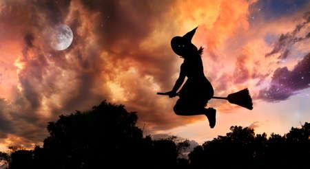 escoba: Silueta de bruja de Halloween con ojos brillantes volando sobre escoba en la noche a cielo dramático con la Luna y las estrellas