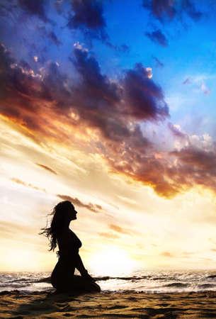 Yoga Vajrasana donder of diamant kunnen opleveren doordat mooie vrouw silhouet op het zand strand en de oceaan in de buurt van zonsondergang achtergrond in India, Goa