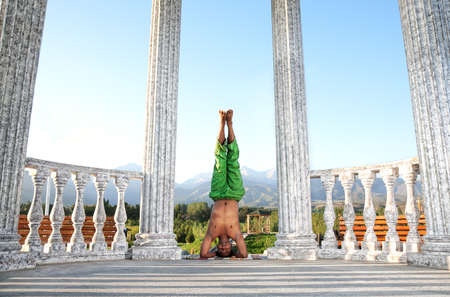 shirshasana: Yoga shirshasana, head standing pose by Indian man in green trousers near stone column at mountain and blue sky background