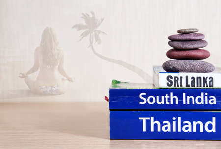guides: Guide books on the table with ayurveda massage stones on its. Woman in yoga meditation with palm tree at background. Books with titles: South India, Sri Lanka, Thailand