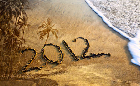 2012 new year message on the sand beach near the ocean with palm trees texture background. Free space for text photo