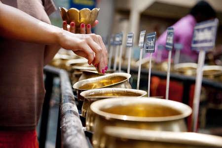 rituals: woman with bowl of 108 coins doing ritual of worshiping to Lord Shiva with mantra Om Namah Shivaya. Bangalore, India, Shiva temple
