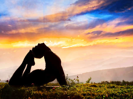 Yoga Raja Kapotasana backward bending pose by Man in silhouette on the grass outdoors at mountains and cloudy sky with sunrays background photo