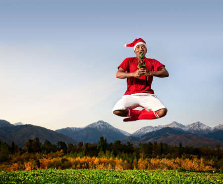 Jumping yoga by Indian man in padmasana lotus pose with Christmas tree in white trousers, red socks and Christmas hat at mountain background. Free space for text photo